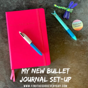 My new Bullet Journal set-up. Image shows my Flying Tiger Journal, 2 pens, a dragonfly ornament and a Find the Good Everyday sticker.