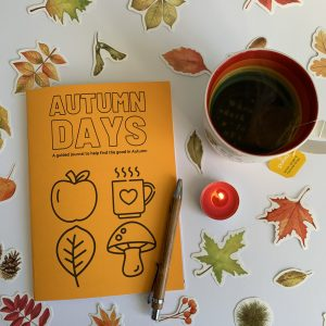Photo of printed Autumn Days Guided Journal surrounded my Autumn stickers. A cup of tea, a lit tea light candle and a pen also feature.